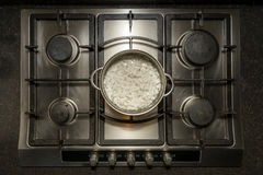 Cooking white rice in water in a metal pan on an iron stove Stock Image