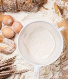 Cooking. White sieve with flour and bread Royalty Free Stock Photography