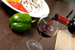 Cooking wine. Filling a glass of wine while cooking Stock Images