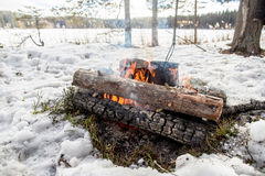 Cooking in a winter hike in the cauldron hanging over the fire Royalty Free Stock Image