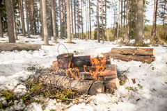 Cooking in a winter hike in the cauldron hanging over the fire Royalty Free Stock Images