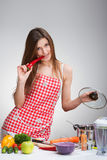 Cooking woman biting the paprika Royalty Free Stock Photo