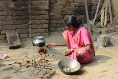 Cooking. A woman is cooking rice in a remote village. Stock Photos