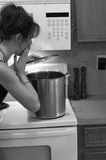 Cooking. Woman looks surprised as she looks into the pot Royalty Free Stock Photo
