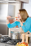 Cooking - Woman tasting tomato sauce in kitchen Royalty Free Stock Photo