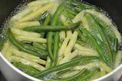 Cooking Yellow and Green Beans. Boiling green and yellow wax beans in some water on the stove in a sauce pan stock images