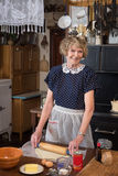 Cooking for you. A happy grandmother making a pie  dressed in vintage clothing in a kitchen from 1940 Stock Photography