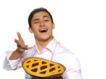 Cooking. Young man in apron baked tasty pie Royalty Free Stock Images