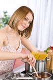 Cooking - Young woman in kitchen Royalty Free Stock Photos