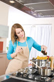 Cooking - Young woman with spaghetti on stove Stock Photos