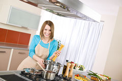 Cooking - Young woman with spaghetti on stove Royalty Free Stock Photography