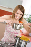 Cooking - Young woman tasting Italian tomato sauce Royalty Free Stock Photography