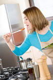 Cooking - Young woman tasting sauce in kitchen Stock Photo