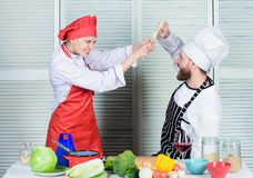 Cooking with your spouse can strengthen relationships. Couple compete in culinary arts. Woman and bearded man culinary. Cooking with your spouse can strengthen royalty free stock images