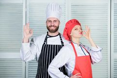 Cooking with your spouse can strengthen relationships. Reasons couples cooking together. Teamwork in kitchen. Couple. Cooking dinner. Woman and bearded men stock photography
