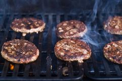 Cookout With Hamburgers. Hamburgers being cooking on an outdoor BBQ grill with smoke Stock Photography