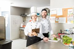Cooks With Clipboard And Vegetables In Kitchen. Portrait of confident chefs working together in kitchen at restaurant royalty free stock image
