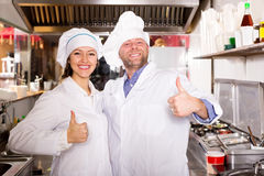 Cooks cooking at professional kitchen Stock Image