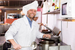 Cooks cooking at professional kitchen Stock Photos