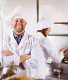 Cooks cooking at professional kitchen Stock Photography
