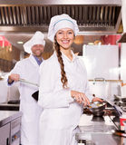 Cooks cooking at professional kitchen Royalty Free Stock Images