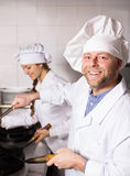 Cooks cooking at professional kitchen Stock Photo