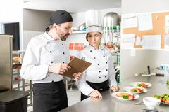 Cooks Going Through Checklist In Kitchen. Male and female chefs discussing over clipboard while preparing dish in kitchen royalty free stock photography