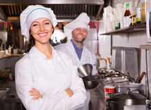 Cooks greeting customers at bistro. Hospitable smiling young cooks greeting customers at bistro kitchen stock photography
