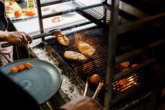 Cooks grilled meat on fire Stock Photos