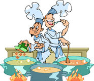 Cooks in the kitchen. Couple of cooks in the kitchen busy cooking a meal Stock Photo