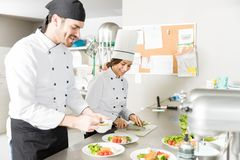 Cooks Smiling While Working In Kitchen. Smiling male and female chefs preparing food together in commercial kitchen stock images