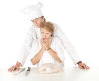Cooks team preparing raw chicken Royalty Free Stock Photos