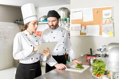 Cooks Using Tablet Computer In Restaurant Kitchen. Male and female chefs reading recipes on digital tablet in kitchen stock photography