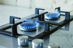 Cooktop with burning gas ring. Gas cooker with blue flames. Tinted photo.  Royalty Free Stock Photography