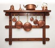 Cookware de cobre del vintage colgado en estante de madera foto de archivo libre de regalías