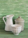 Cookware do vintage - frasco esmaltado, jarro e bacia cerâmica branca em uma superfície de madeira verde Fotografia de Stock