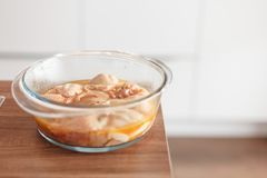 Cookware en verre avec un poulet mariné Image stock