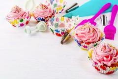 Cookware och muffin med den rosa färger piskade kräm- virveln, kopieringsutrymme Royaltyfria Foton