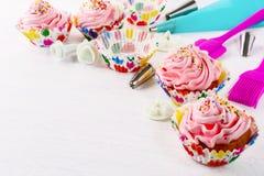 Cookware- och rosa färgfödelsedagmuffin Arkivbild