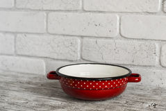 Cookware - red with white dots enameled bowl on bright wooden table. Stock Photos
