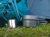 Cookware voor het kamperen is op het gras op de achtergrond van een rug Stock Foto