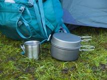 Cookware voor het kamperen is op het gras op de achtergrond van een rug Royalty-vrije Stock Foto