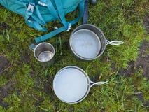 Cookware voor het kamperen is op het gras op de achtergrond van een rug Royalty-vrije Stock Afbeeldingen
