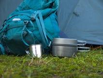 Cookware voor het kamperen is op het gras op de achtergrond van een rug Stock Fotografie