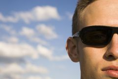 So cool. Half facial portrait of a young amn with cool sunglasses and slightly cloudy sky background. Very narrow selectiv focus to emphasize the relaxed, cool royalty free stock images