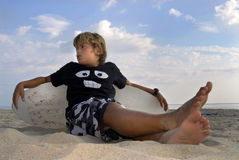 Cool. Boy posing in the beach with a skimboard Royalty Free Stock Image