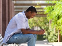 Cool african american guy looking at cell phone Royalty Free Stock Image