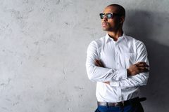 Cool african businessman standing on grey background. stock photo