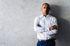 Cool african businessman standing on grey background. stock photography
