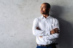 Cool african businessman standing on grey background. royalty free stock photos